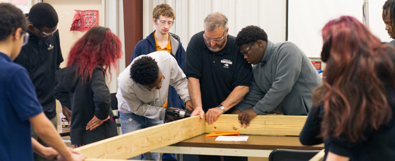 Students and teacher at Countryside Academy constructing a woodworking project.