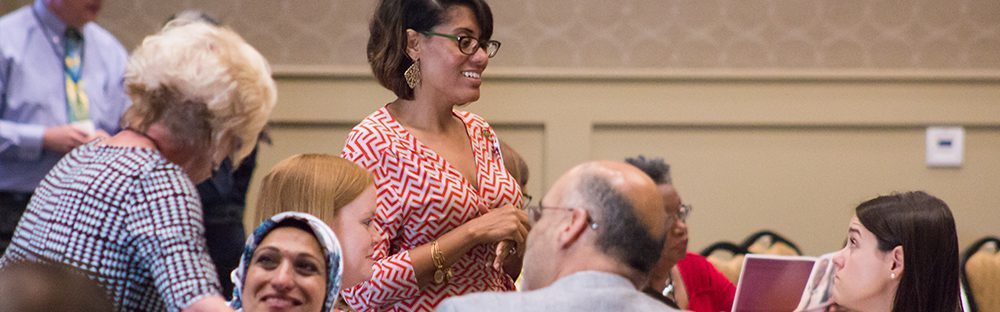 Photo of staff talking with attendees at the Center's annual conference.